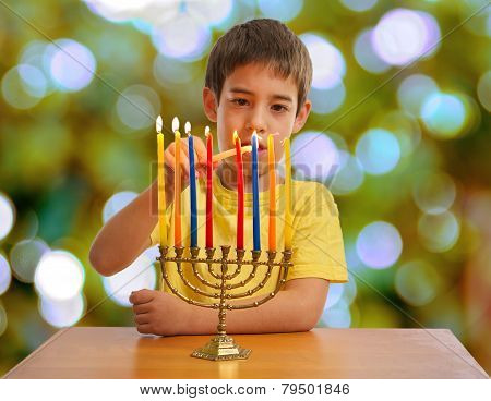 Israeli Boy Lighting A Hannukah Menorah