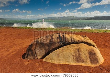 Large Stone By Lake Arenal With A Windsurfer