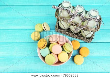 Assortment of gentle colorful macaroons in colorful bowl milk bottles on color wooden background