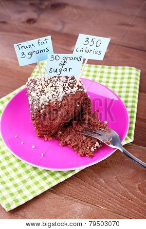 Chocolate cake with calories count labels and fork on color plate and napkin, on wooden table background