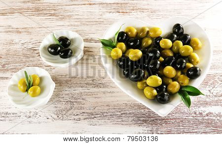 Plates with black and green olives on painted wooden background