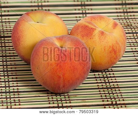 Three Ripe Peaches On Wicker Straw Mat