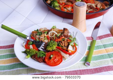 Braised wild mushrooms with vegetables and spices in pan and plate on table