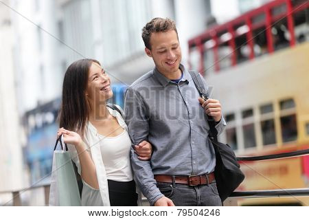 Hong Kong couple shopping in Central walking in streets with shopping bags. Urban mixed race Asian Chinese woman shopper and Caucasian man smiling happy living in city.
