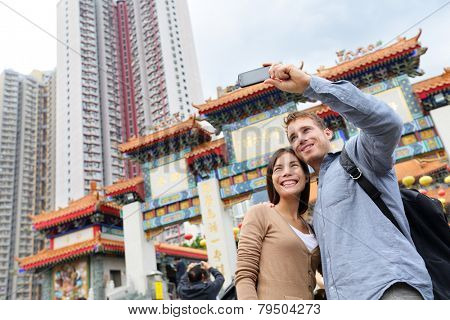 Hong Kong tourist attraction Wong Tai Sin Temple. Tourists taking selfie photo pictures by famous Hong Kong landmark. Romantic couple visiting and sightseeing Taoist temple. Asian woman, Caucasian man