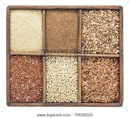 a variety of gluten free grains (buckwheat, amaranth, brown rice, millet, sorghum, teff,  red quinoa) in a rustic wooden box isolated on white