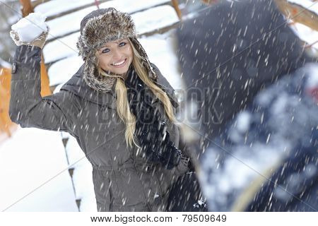 Happy young woman throwing snowball. Outdoor photo.
