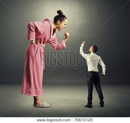 displeased wife screaming at her husband over dark background
