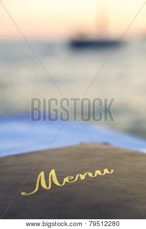 A menu laid on a seafood restaurant table with a boat out of focus on the sea at sunset in the background