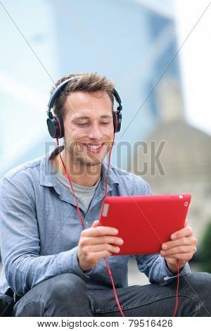 Video chat conversation. Man talking on tablet pc sitting outside using app on 4g wireless device wearing headphones. Casual young urban professional male in his late 20s.