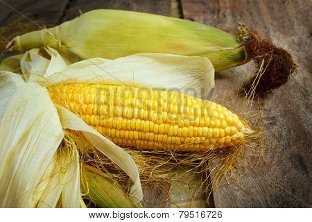 Corn Cobs On Wood Background.