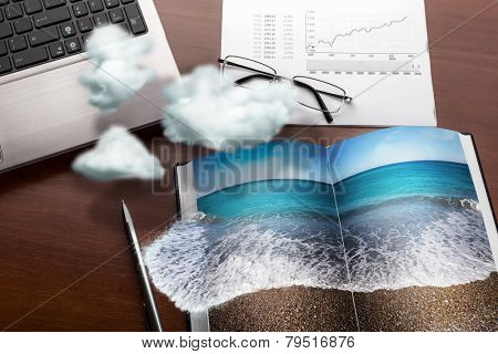 Office table in clouds with the sea on the notebook. Vacation concept