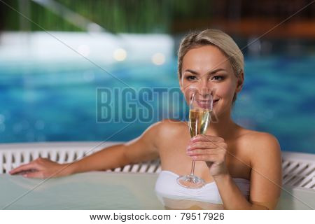 people, beauty, spa, healthy lifestyle and relaxation concept - beautiful young woman wearing bikini swimsuit sitting with glass of champagne in jacuzzi at poolside