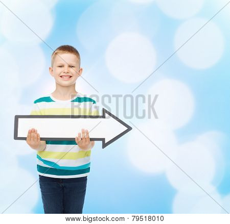 advertising, direction and childhood concept - smiling little boy with white blank arrow pointing right over blue background