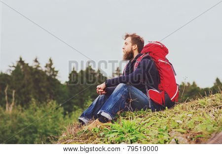 adventure, travel, tourism, hike and people concept - man with beard and red backpack sitting on ground