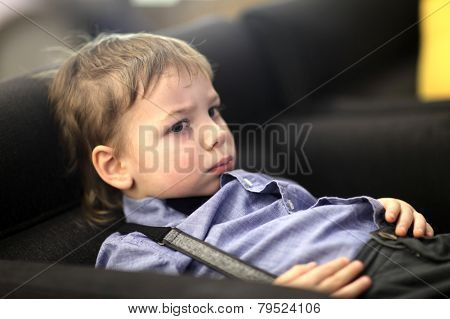 Pensive Child On Sofa