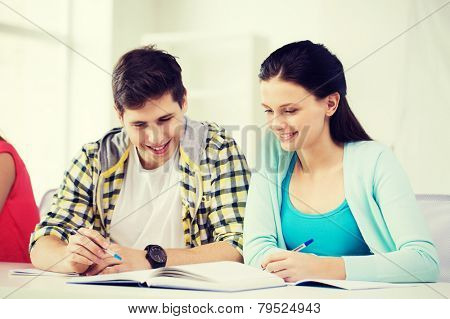 education and school concept - two smiling students with textbooks and books at school