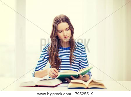 education and home concept - concecntrated student girl with books