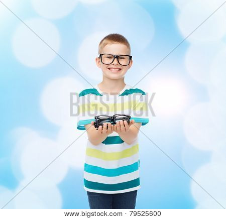 vision, health and people concept - smiling little boy in eyeglasses holding spectacles over blue background