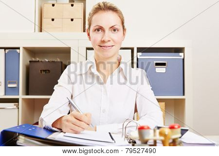 Young smiling businesswoman working at her desk in the office