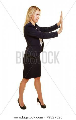Young businesswoman pushing imaginary object to the side