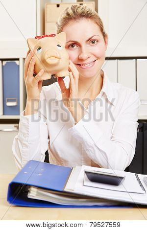 Smiling young business woman at her desk in the office holding a piggy bank