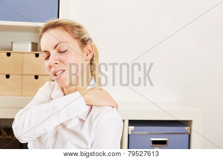 Business woman standing in office with pain in her shoulder