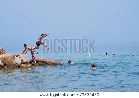 GREECE - JUNE 26: Boys jumps from a rocks into the sea on a sunny day on June 26,2014 on the beach in Nikiti, Sithonia peninsula, Greece.
