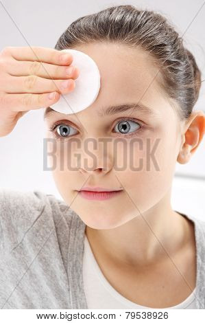 Beautiful a young teenager cleanses the facial skin tonic