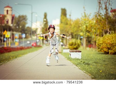 little cute happy girl rollerblading through the city streets