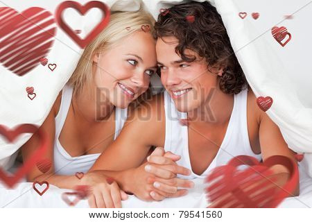 Portrait of an in love couple under a duvet against love heart pattern