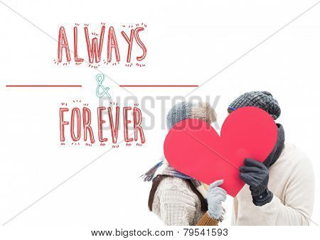 Attractive young couple in warm clothes holding red heart against always and forever