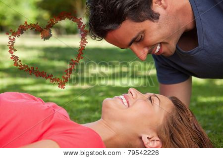 Man smiling as he looks down into his friends eyes against heart made of petals
