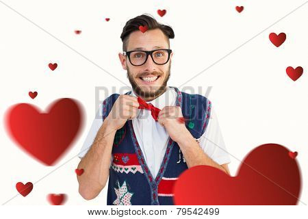 Geeky hipster wearing christmas vest against hearts