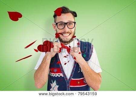 Geeky hipster wearing christmas vest against green vignette