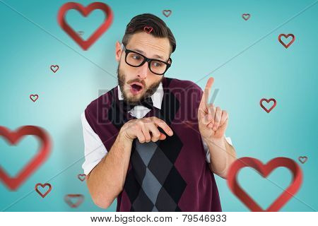 Geeky hipster in sweater vest pointing against blue vignette background