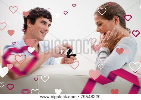 Man making a proposal of marriage against love heart pattern
