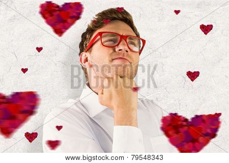 Young geeky businessman with hand on chin against parchment