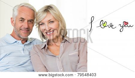 Smiling mature couple sitting on sofa with arm around against i love you