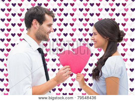 Pretty brunette giving boyfriend her heart against valentines day pattern