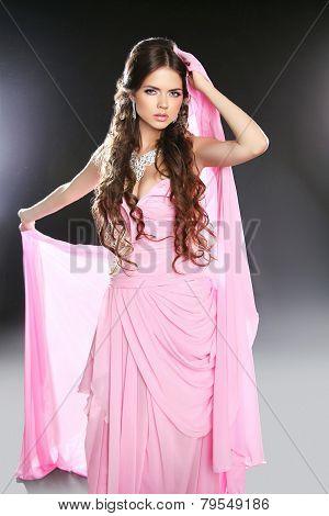 Beautiful Young Woman In Pink Chiffon Dress. Makeup. Long Wavy Hair Styling. Studio Photo.