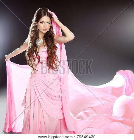 Beautiful Brunette Girl Model In Blowing Transparent Chiffon Dress. Long Wavy Hair Styling.