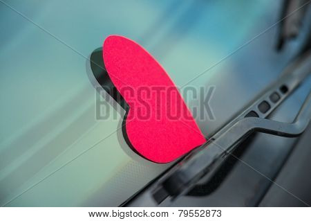 Paper shaped heart on the car window