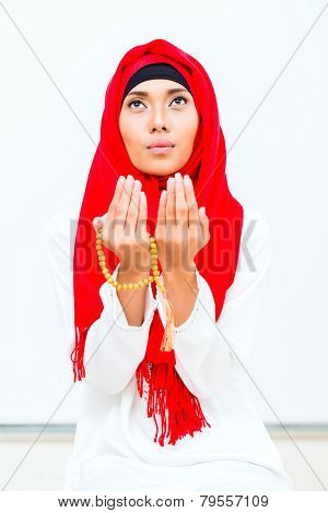 Asian Muslim woman praying with beads chain wearing traditional dress