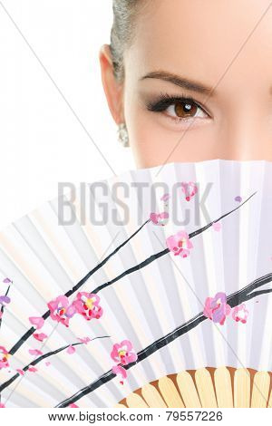Asian chinese woman looking seductive with paper fan. Beauty portrait of female model face with closeup on eyes.