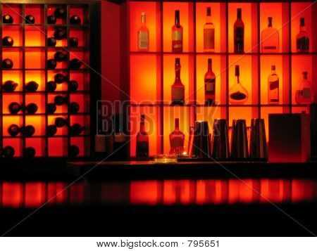 Ambient lighting reflecting of a bar with bottles of spirits and wine ...
