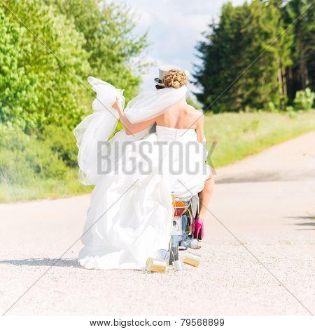 Wedding groom and bride driving motor scooter having fun