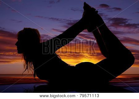 Silhouette Of A Woman On Her Stomach Reach Back Hold Feet