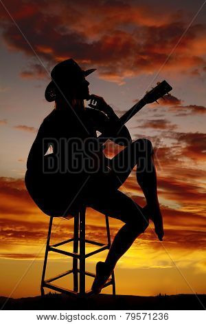 Silhouette Of A Woman With A Guitar Hand Under Chin