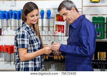 Side view of male vendor showing wrench to female customer in hardware shop